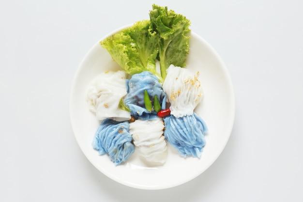 Parcelles de riz cuit à la vapeur de porc isolé nourriture dessert asiatique thaï sur table en bois