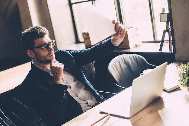 En parcourant les derniers chiffres. gentil jeune homme en tenue décontractée intelligente tenant du papier et le regardant travailler sur un ordinateur portable alors qu'il était assis sur son lieu de travail au bureau