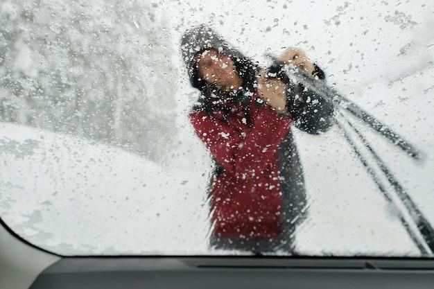 Pare-brise glacé avec une personne floue grattant la glace sur un essuie-glace, conduite hivernale à travers une tempête de neige