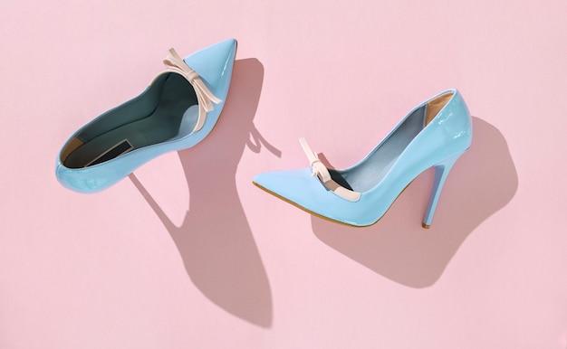 Pare de chaussures à talons hauts bleu clair sur fond rose