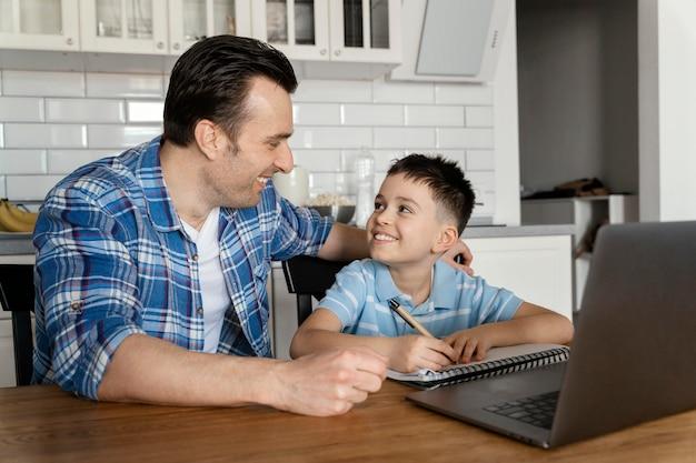 Parent et enfant de tir moyen avec ordinateur portable