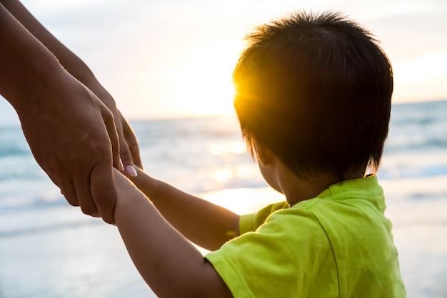 Le parent de focus doux tient la main du petit enfant pendant le coucher du soleil