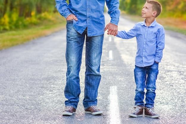 Un parent heureux avec un enfant dans le parc mains sur le voyage de la nature aller le long de la route