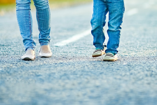Un parent heureux avec enfant marchent le long de la route dans le parc lors d'un voyage dans la nature