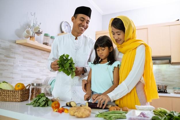 Parent musulman et enfant cuisinant et préparant un dîner iftar ensemble dans la cuisine