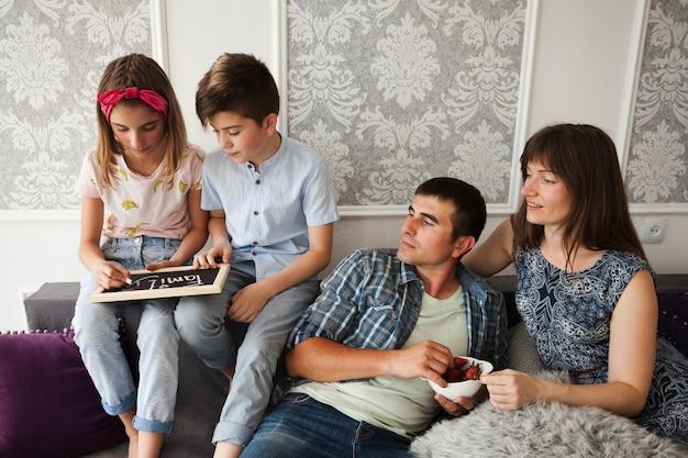 Un parent regarde ses enfants tout en écrivant un texte de famille sur une ardoise