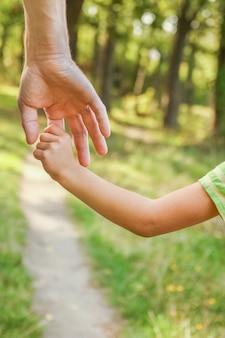 Le parent tenant la main de l'enfant avec une surface heureuse