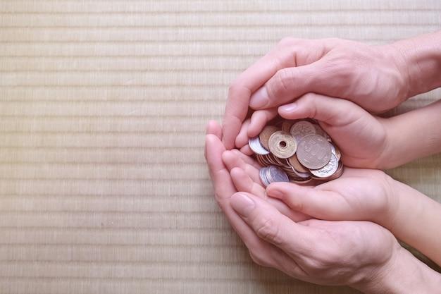 Parent tenant des mains d'enfant avec de l'argent japonais