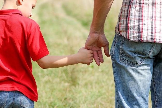 Le parent tient la main d'un petit enfant sur la nature