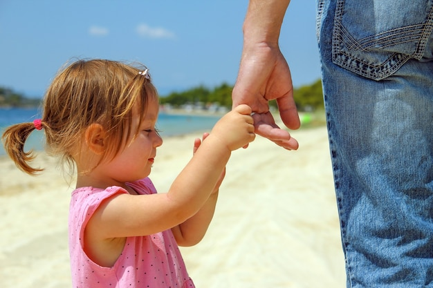 Le parent tient la main d'un petit enfant sur la plage près de la mer