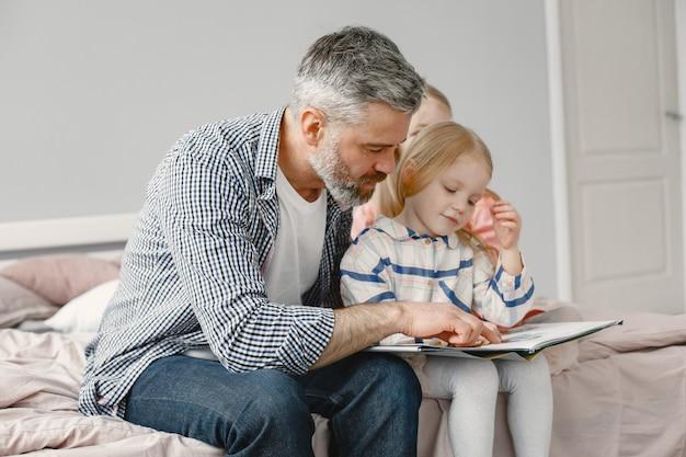 La parentalité. jolie fille assise avec grand-père dans la chambre. lire ensemble un livre.