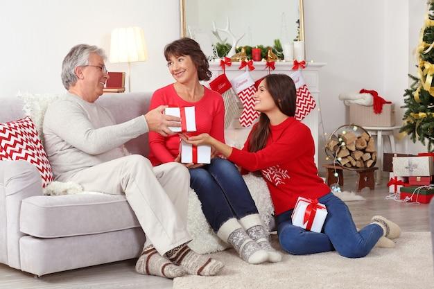 Les parents âgés et leur fille se donnent des cadeaux de noël