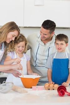 Parents aidant les enfants à préparer des biscuits