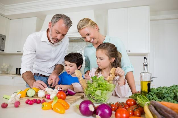 Les parents aident les enfants à couper les légumes