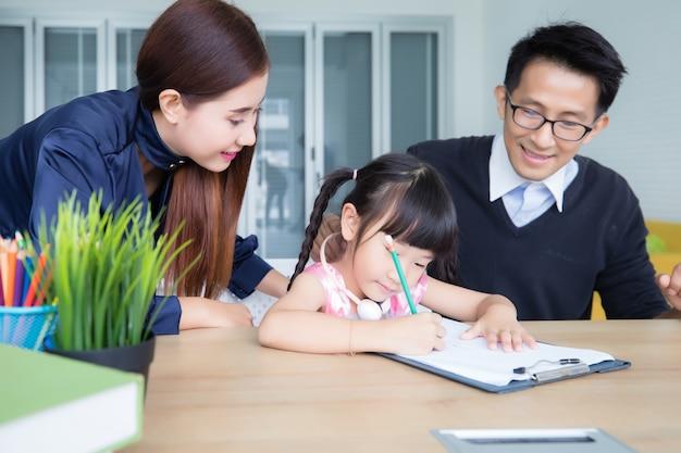 Les parents aident à enseigner les devoirs de leur fille. la jeune fille écrit le livre avec détermination concept home school