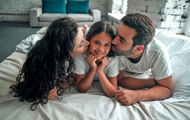 Parents aimants embrassant leur fille allongée sur un lit