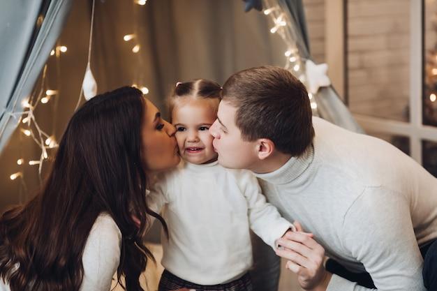 Parents aimants embrassant leur jolie fille sur les joues.