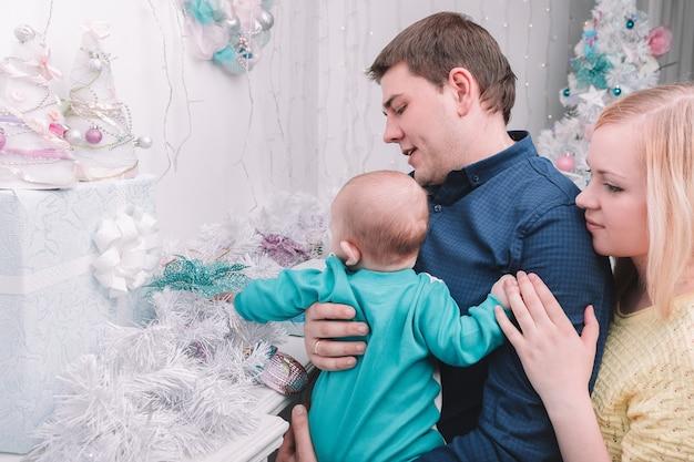 Des parents aimants montrent à leur bébé des cadeaux de noël. le concept de noël