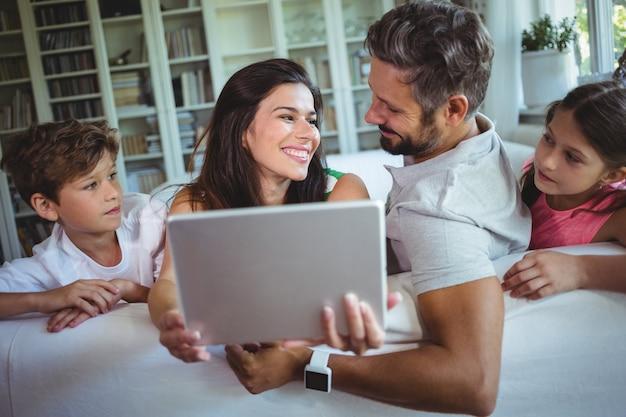 Parents assis sur un canapé avec leurs enfants et utilisant une tablette numérique dans le salon