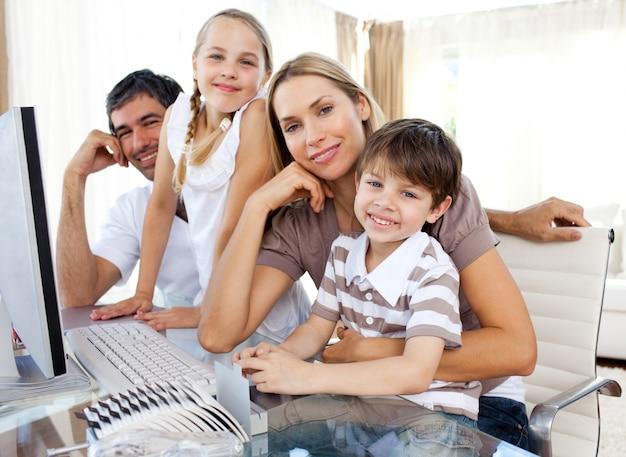 Les parents attentifs et leurs enfants utilisent un ordinateur