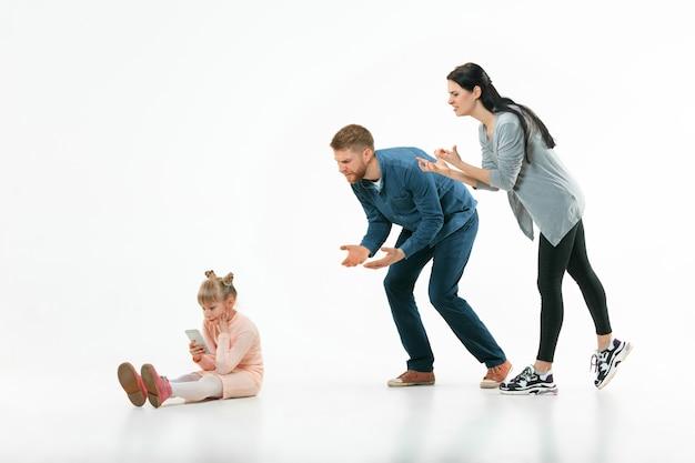 Des parents en colère grondent leur fille à la maison. photo de studio de famille émotionnelle. les émotions humaines, l'enfance, les problèmes, les conflits, la vie domestique, le concept de relation