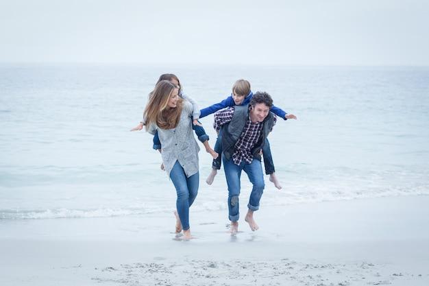 Parents courir en portant des enfants au bord de la mer