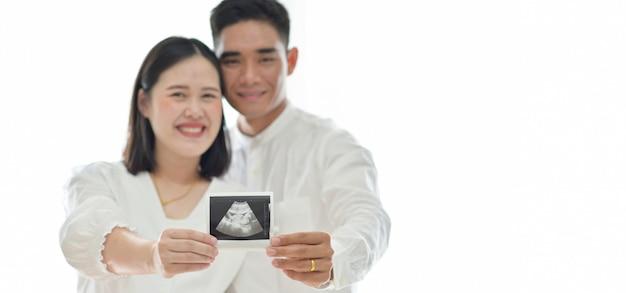 Les parents détiennent des résultats d'échographie du fœtus.