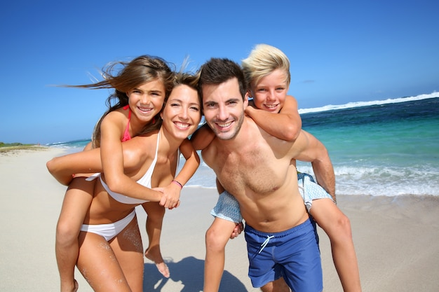 Parents donnant aux enfants à la plage une promenade sur le dos