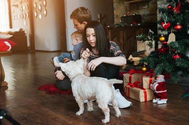 Les parents et un enfant jouant avec le chien
