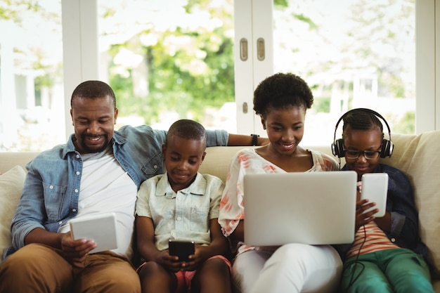 Parents et enfants à l'aide d'un ordinateur portable, d'un smartphone et d'une tablette numérique sur un canapé