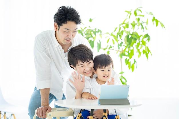 Parents et enfants asiatiques communiquant en ligne à l'aide d'une tablette pc