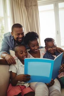 Parents et enfants assis ensemble sur un canapé avec album photo