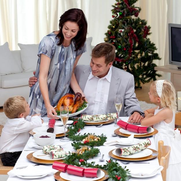 Parents et enfants au dîner de noël avec la turquie