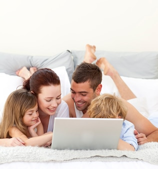 Parents et enfants au lit jouant avec un ordinateur portable