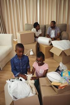 Parents et enfants déballant des boîtes en carton dans le salon