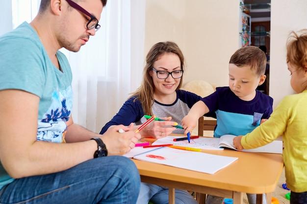 Parents et enfants dessinent ensemble dans la pièce