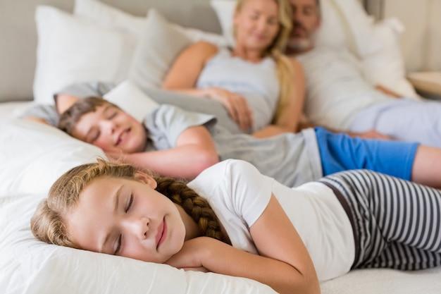 Parents et enfants dormant sur le lit dans la chambre