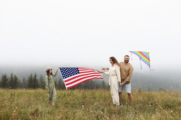 Les parents et les enfants avec le drapeau américain jouent avec un cerf-volant coloré. mère, père et petite fille célèbrent ensemble le 4 juillet à l'extérieur par temps brumeux. concept de la fête de l'indépendance des etats-unis.