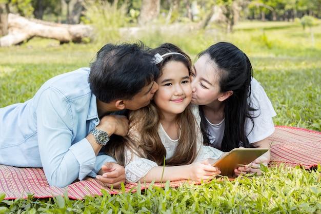 Les parents et les enfants jouent à la tablette sur le tapis.