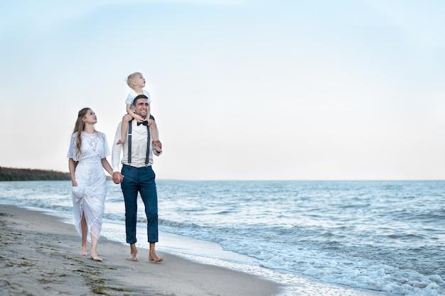 Parents et enfants marchant au bord de l'océan au coucher du soleil. vacances en mer avec des enfants