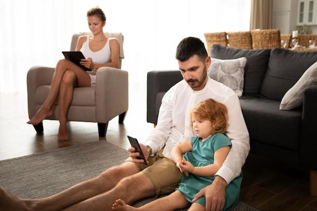 Parents et enfants de plan moyen avec des appareils