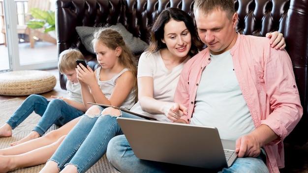 Parents et enfants à plan moyen avec des gadgets