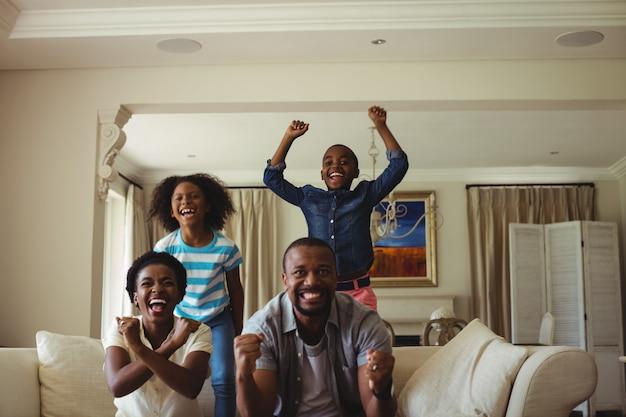 Parents et enfants s'amusent en regardant la télévision dans le salon
