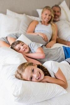 Parents et enfants se détendre sur le lit dans la chambre