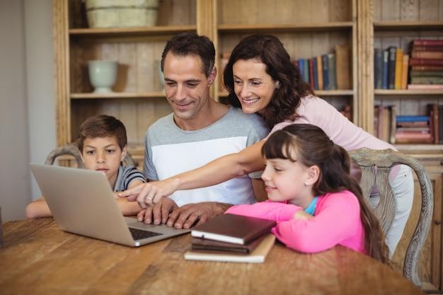Parents, enfants, utilisation, ordinateur portable, table, étude, salle