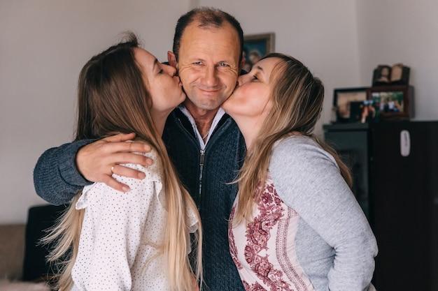 Parents étreignant leur fille et regardant la caméra. sourire. famille.
