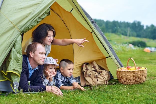 Parents familiaux et deux enfants dans une tente de camp. heureuse mère, père, fils et fille en vacances d'été. maman montrant quelque chose à distance