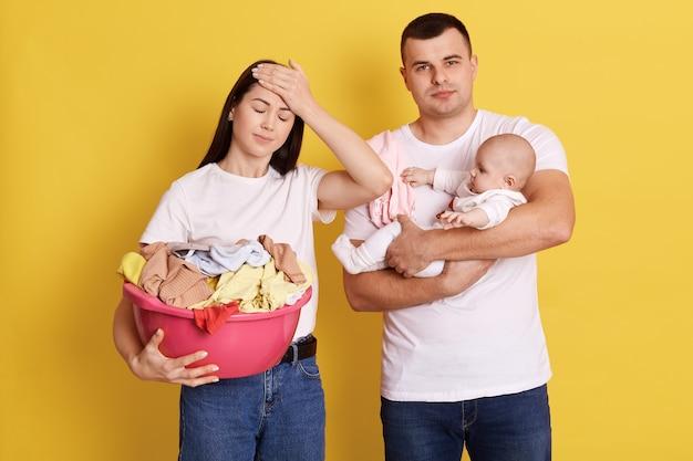 Les parents fatigués font les tâches ménagères et s'occupent du nouveau-né, la mère tient un bassin avec du linge, garde les yeux fermés et touche le front avec la paume, le père porte sa fille avec une expression épuisée.
