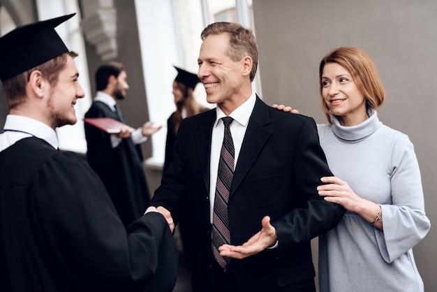 Les parents félicitent l'homme avec la fin des études.