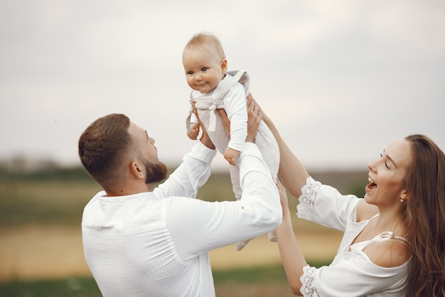Parents avec fille. famille dans un champ. fille nouveau-née. femme en robe blanche.